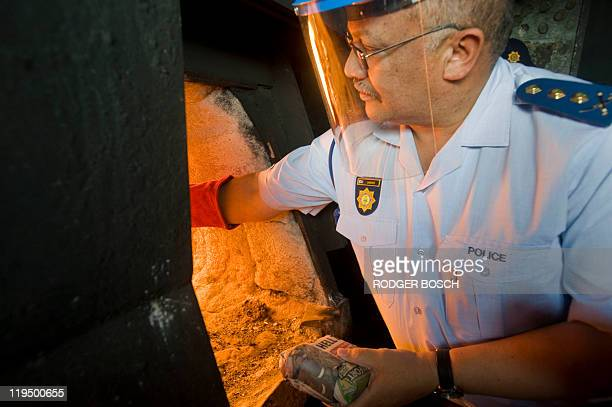 Western Cape Commissioner General Arno Lamoer of the South African Police Services loads parcels of marijuana into an incinerator at the SAPS...