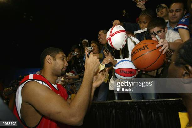 Western Conference AllStar Tim Duncan of the San Antonio Spurs signs autographs for some fans after the Wests' practice for the 2004 NBA AllStar game...
