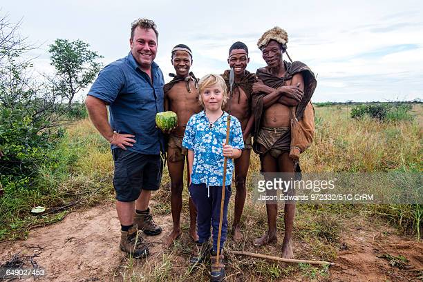 A western father and son with the men of a San Bushmen family in the Kalahari