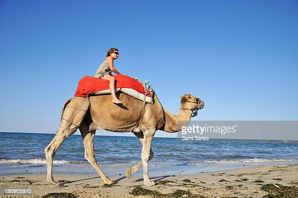 western girl riding a camel on beach, by sea - djerba photos et images de collection