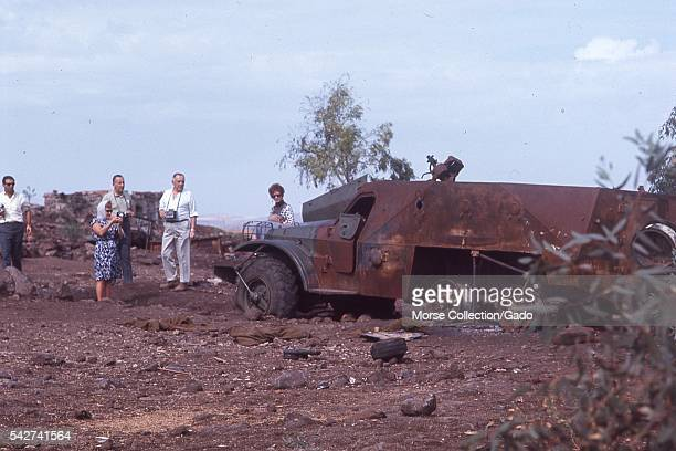Western male and female tourists posing among the destroyed military vehicles and armament from the Six Day War located outside of the town of...