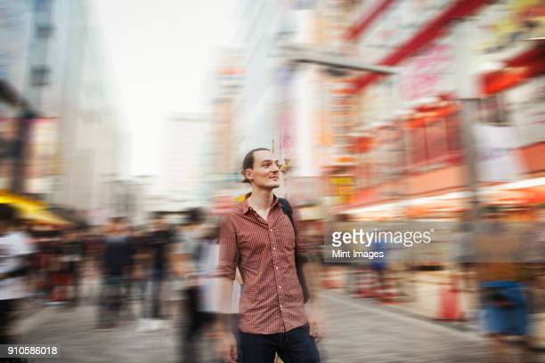 a western man in tokyo on the street, looking around him. long exposure, blurred background effect. - long exposure stock pictures, royalty-free photos & images