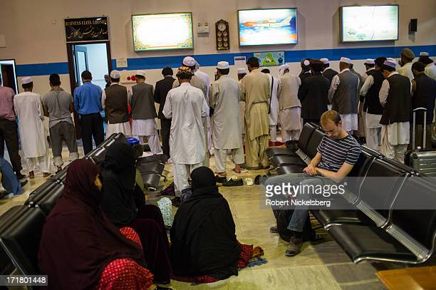 Western man reads as Afghans stand during evening prayers May 16, 2013 in the departure lounge at Kabul International Airport in Kabul, Afghanistan....