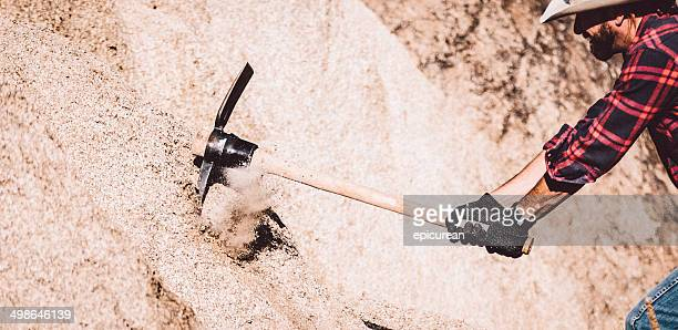 Western Man swings pickaxe against rock face