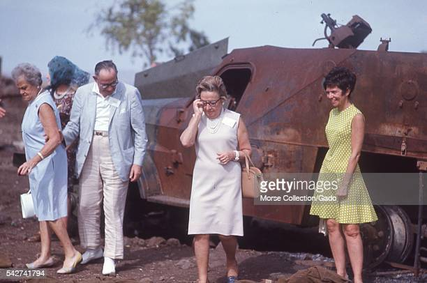 Western men and women posing in front of a rusted and burned military vehicle from the Six Day War in the Golan Heights outside the town of Quneitra...