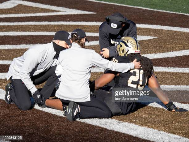 Western Michigan Broncos head coach Tim Lester checks on Western Michigan Broncos linebacker Corvin Moment during the college football game between...