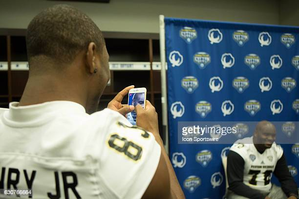 Western Michigan Broncos wide receiver Michael Henry takes pictures of Western Michigan Broncos offensive lineman Taylor Moton while he's being...