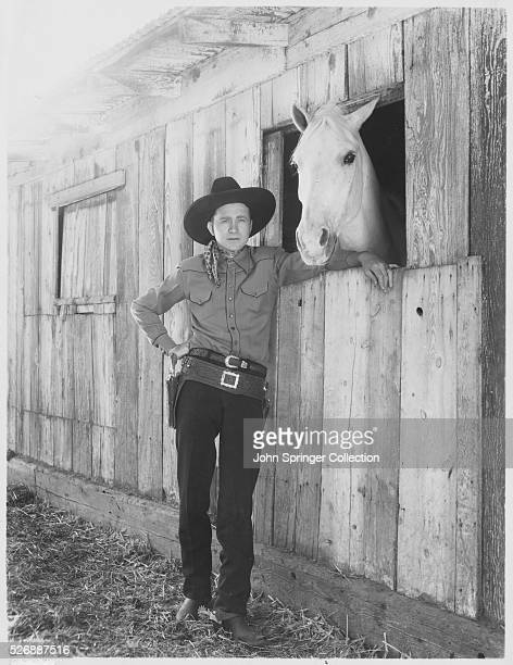 Western movie star Tex Ritter stands with his horse White Flash