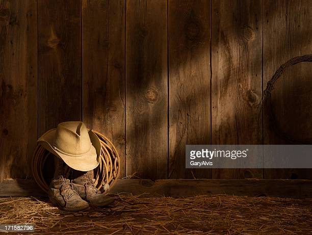 Western packer's boots,hat,lasso on barn floor-sunbeam on barnwood wall
