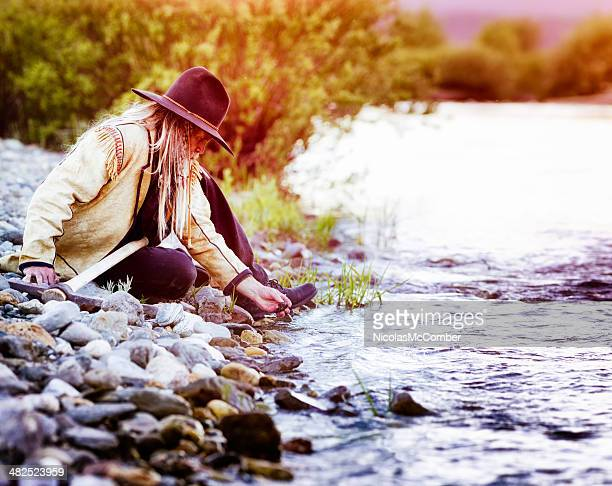 Western prospector picks up pebbles from river bed