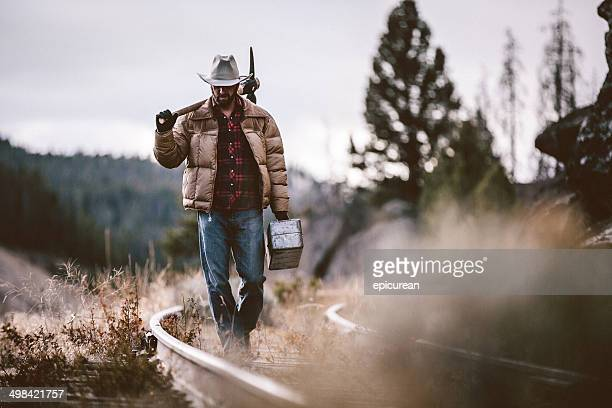 Western rugged man walks along old railroad tracks carrying toolbox