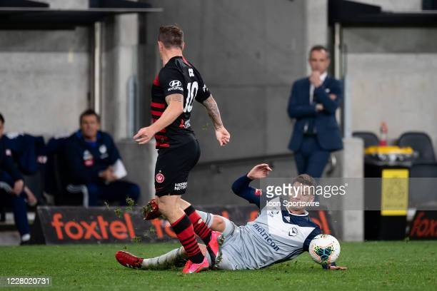 Western Sydney Wanderers midfielder Simon Cox is tackled by Melbourne Victory forward Nils Ola Toivonen during the round 27 A-League soccer match...