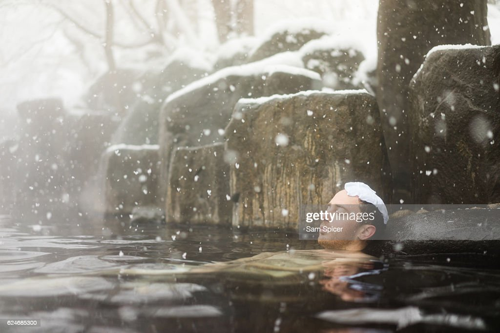 Western tourist enjoying natural hot spring onsen during Winter snow : ストックフォト