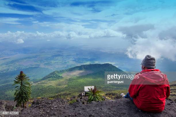western tourist is sitting at the crater of nyiragongo volcano - virunga national park stock pictures, royalty-free photos & images