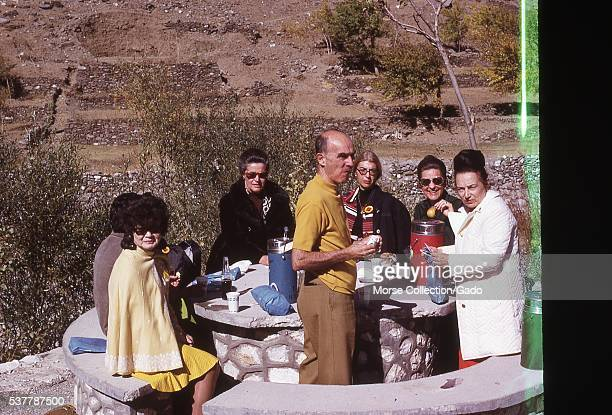 Western tourists eating lunch at an outdoor rest stop in the mountains outside of Kabul, Afghanistan. Damage present on original photograph....