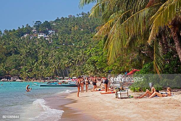 Western tourists sunbathing on beach of Ko Tao / Koh Tao island and part of the Chumphon Archipelago in Southern Thailand