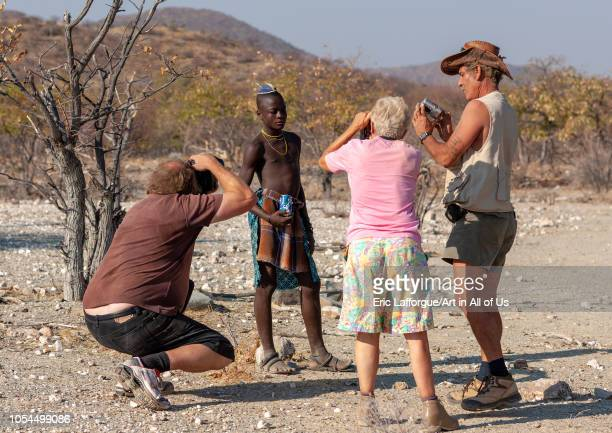 Western tourists taking pictures of a Himba tribe young man, Cunene Province, Oncocua, Angola on August 12, 2010 in Oncocua, Angola.