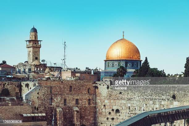 western wall with golden dome of the rock mosque against blue sky - palestijnse gebieden stockfoto's en -beelden