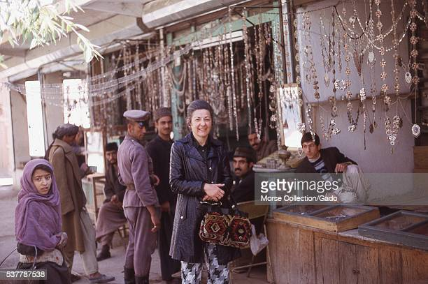 Western woman poses in front of a metalwork jewelry stall at the market in Kabul, Afghanistan, as local Afghanis look on. November, 1973. .