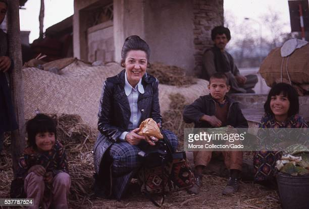 Western woman poses with Afghani children at the melon market in Kabul, Afghanistan. November, 1973. .