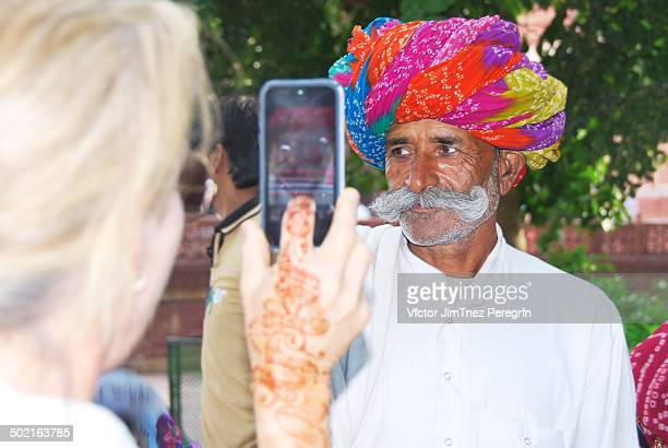CONTENT] Western woman with a henna tattoo taking a mobile photo of a local Indian tribe