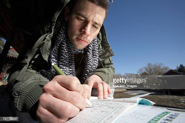 Westerner practices his Chinese characters in a garden at the Summer Palace