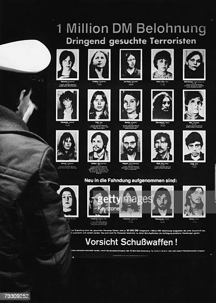 A WestGerman policeman reading a wanted poster offering a onemillionmark reward for information leading to the capture of 20 members of the...