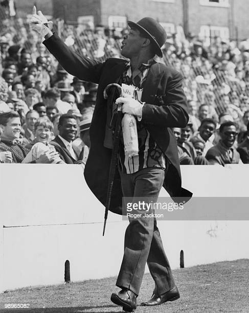 A WestIndian supporter with a rolled up umbrella and a bowler hat leads the cheers during the Fifth and final Test against England at the Oval London...