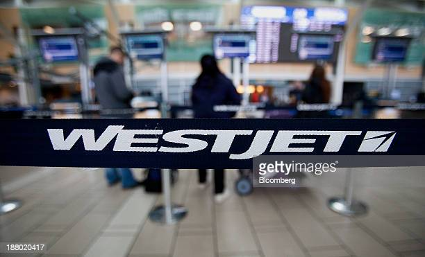 Westjet Airlines Ltd signage is displayed on a band as travelers stand in line at Vancouver International Airport in Richmond British Columbia Canada...