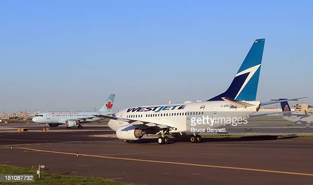 WestJet flight and an Air Canada flight cross paths on a runway at the Lester B Pearson airport as photographed from an airplane on August 28 2012 in...