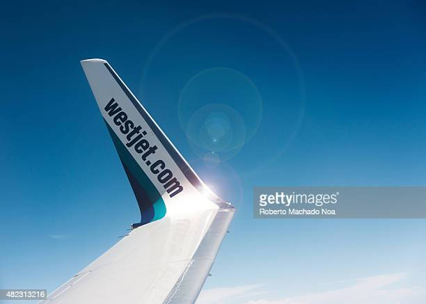 Westjet winglet while the plane is flying seen over a blue sky and with enhancing flares caused by a light reflection over the metal