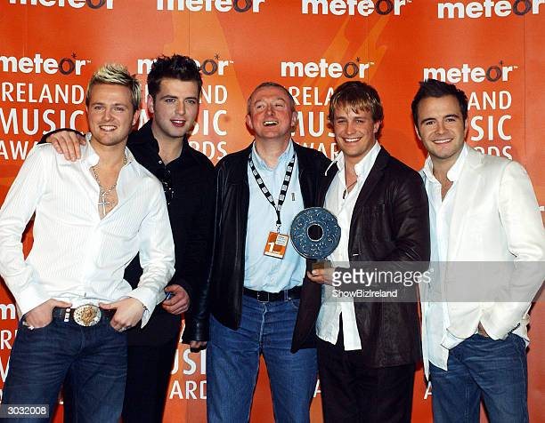Westlife pose with Louis Walsh at a photocall prior to The Meteor Ireland Music Awards at the Point Theatre Dublin Ireland March 01 2004