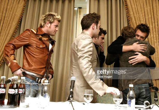 Westlife's Bryan McFadden embraces bandmates Shane Filan Mark Feehily Kian Egan and Nicky Byrne at a press conference announcing Bryan McFadden is to...
