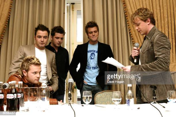 Westlife's Kian Egan reads a statement as his bandmates Nicky Byrne Shane Filan Mark Feehily and Bryan McFadden look on at a press conference...