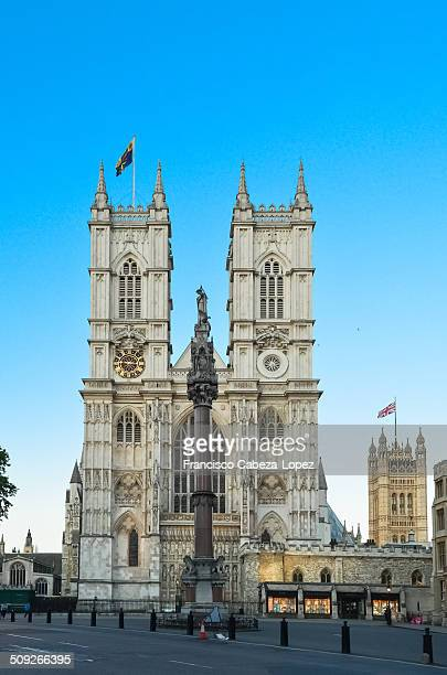 Westminster Abbey, Westminster Column and Houses of Parliament illuminated at dusk under clear sky, London.