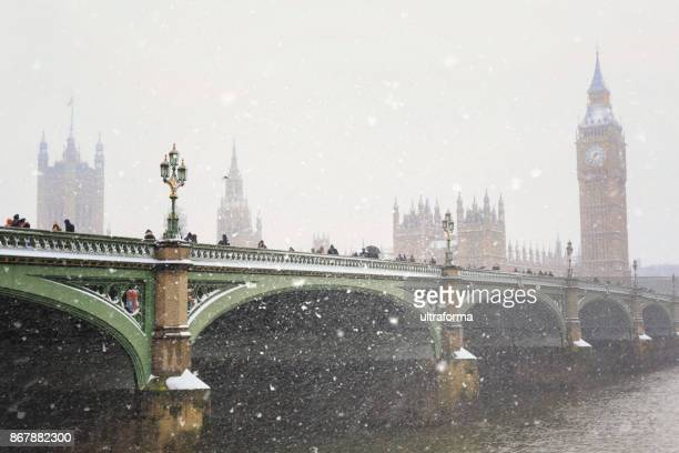 westminster bridge and the houses of parliament during a snowstorm in london - city of westminster london stock photos and pictures