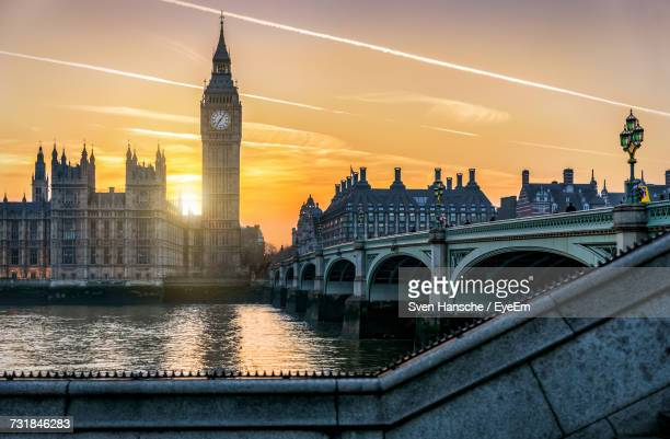 westminster bridge by big ben over thames river against sky during sunset in city - big ben stock pictures, royalty-free photos & images