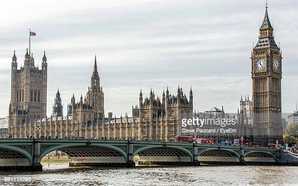 Westminster Bridge Over Thames River By Big Ben And Houses Of Parliament Against Sky