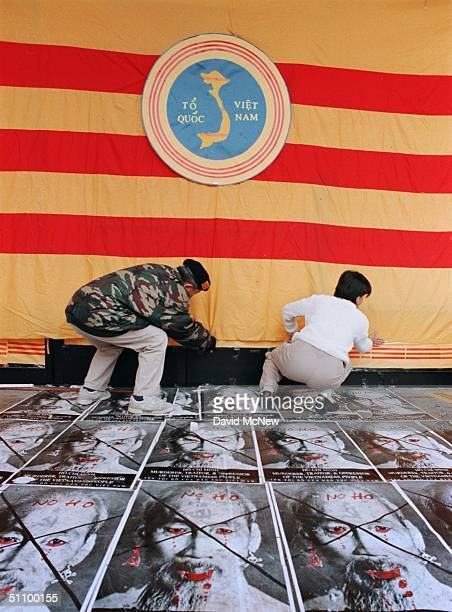 21Feb99 American Vietnamese AntiCommunist Demonstrators Tihn Nguyen And Thu Nga Secure A South Vietnamese Flag That Covers Up Truong Van Tran's...