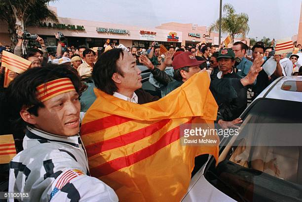 21Feb99 Steven Nguyen And Other Protest Leaders Shout Down An Angry Crowd And Wrap Mr Le In A South Vietnamese Flag Encouraging Him To Shout...