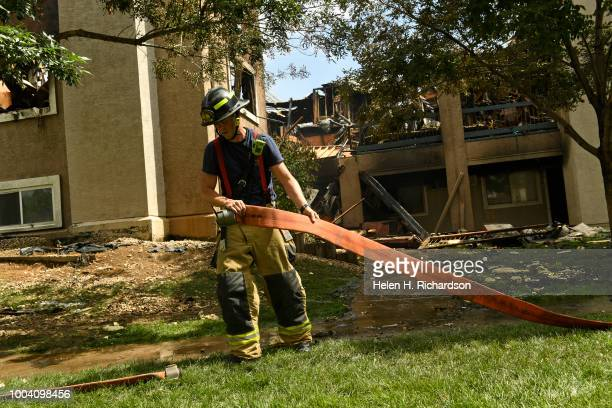 Westminster firefighter cleans up hoses at the scene of a deadly apartment complex fire at the Westbury Apartments on July 22 in Westminster Colorado...