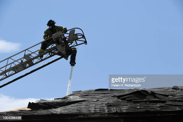 Westminster firefighter puts water on hotspots on the roof at the scene of a deadly apartment complex fire at the Westbury Apartments on July 22 in...