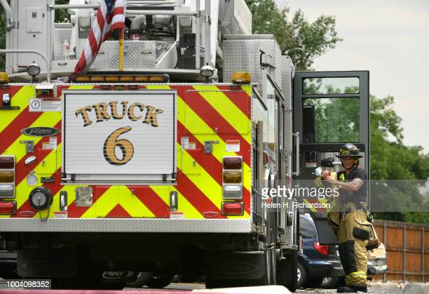 Westminster firefighter takes a break after helping fight fire at the scene of a deadly apartment complex fire at the Westbury Apartments on July 22...