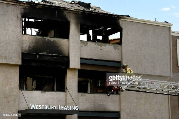 Westminster firefighter walks on the ladder to begin to put water on hotspots at the scene of a deadly apartment complex fire at the Westbury...