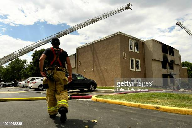Westminster firefighter watches as ladder trucks prepare to put water on hotspots at the scene of a deadly apartment complex fire at the Westbury...