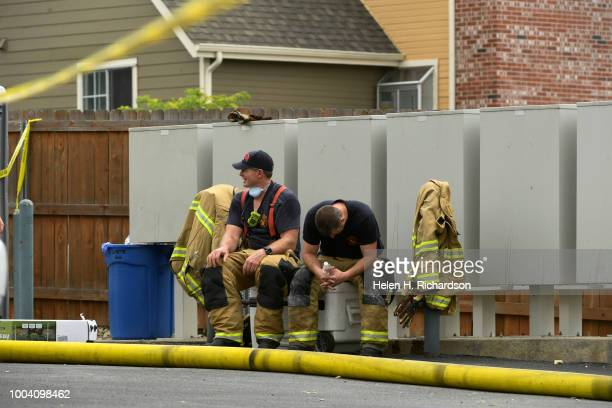 Westminster firefighters take a break after helping fight fire at the scene of a deadly apartment complex fire at the Westbury Apartments on July 22...
