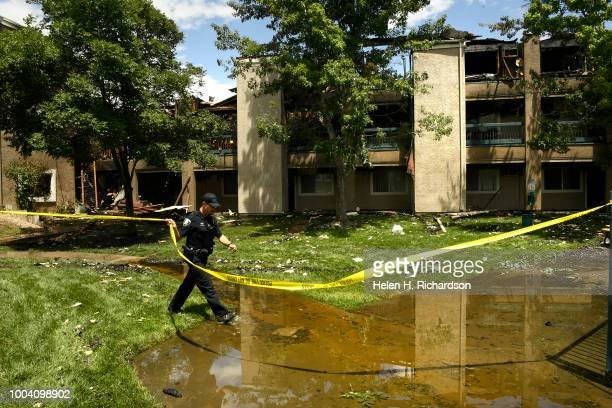 Westminster police officer secures tape around the perimeter of the fire at the scene of a deadly apartment complex fire at the Westbury Apartments...