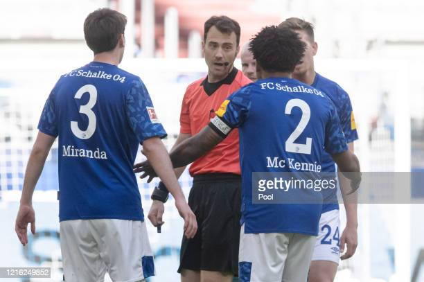 Weston McKennie of FC Schalke 04 wears an armband with the words Justice for George on while he speaks to referee Felix Zwayer during the Bundesliga...