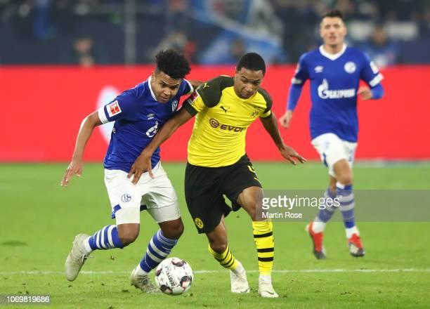 Weston McKennie of FC Schalke shoots challenges for the ball with Abdou Diallo of Borussia Dortmund during the Bundesliga match between FC Schalke 04...