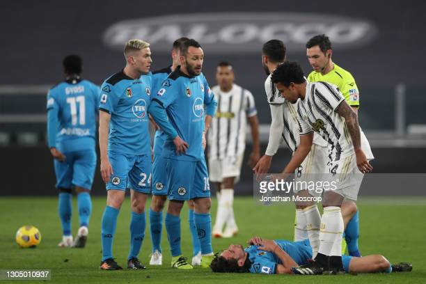 Weston McKennie of Juventus hands a bottle of water to Luca Vignali of Spezia Calcio as he lays injured after clashing with Gianluca Frabotta of...